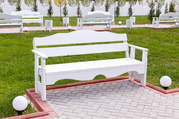 White wooden empty benches in the city park.