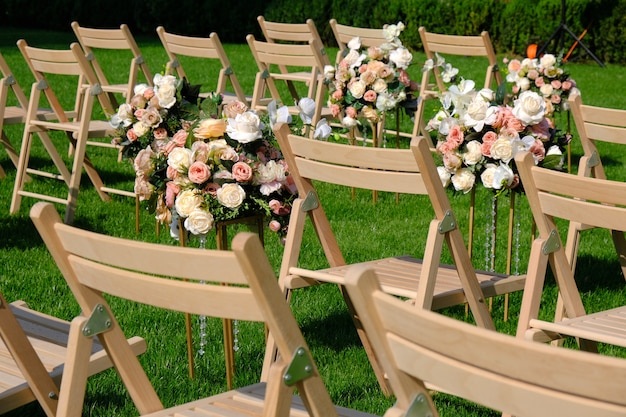 White wooden empty chairs in a row and flowers bouquets on green grass. wedding ceremony decorations.