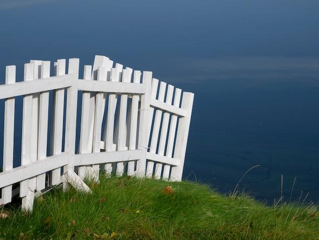 緑の芝生と水と白い木製のフェンス。
