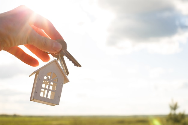 White wooden figure of a house and keys in hand against of the sky and field.