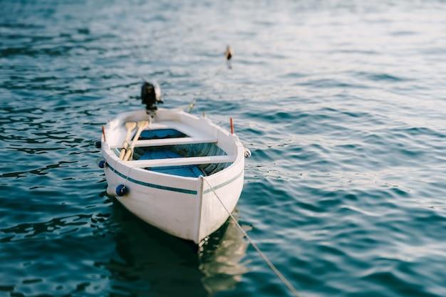Белая деревянная рыбацкая лодка с веслами и мотором