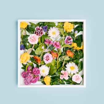 White wooden frame full of flowers.top view mockup with copy space.