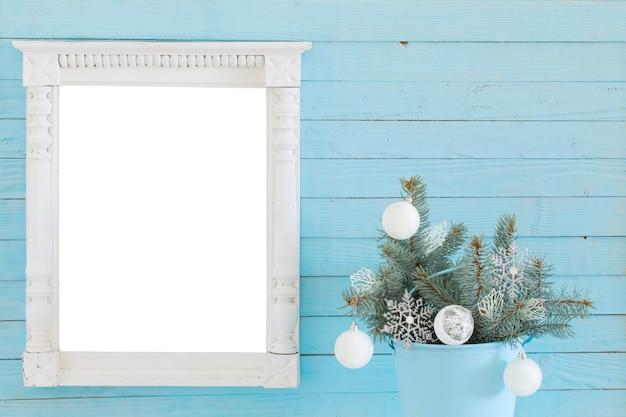 青い木製の背景にクリスマスの装飾が施された白い木製フレーム