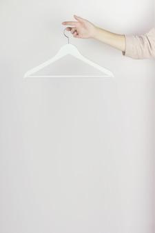 指の手、ファッションの背景にぶら下がっている白い木製ハンガー。春のセールコンセプトディスコウン