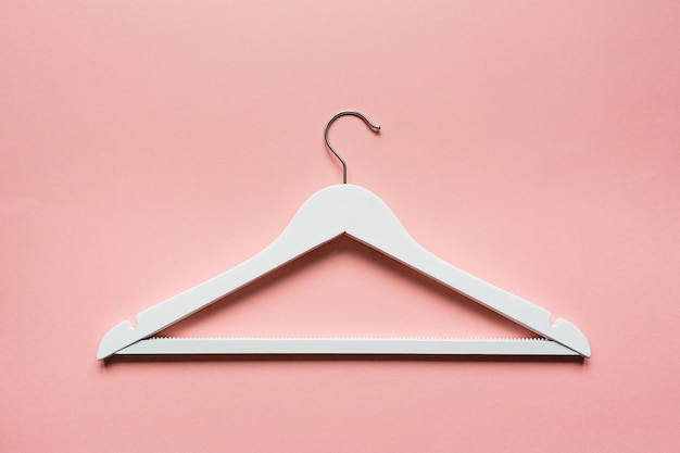 White wooden hanger on pink