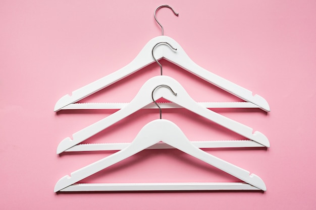 White wooden hangers on pink