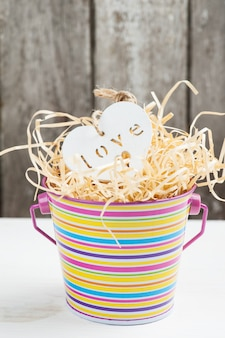 White wooden heart in stripped bucket