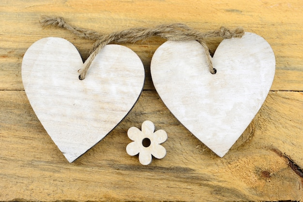 Cuori di legno bianchi e un fiore su una superficie di legno