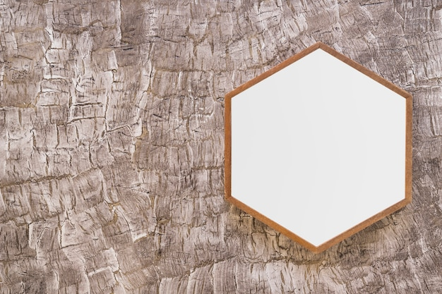 White wooden hexagon frame on painted wall