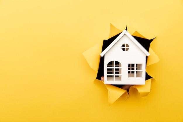 黄色い紙の穴から白い木造住宅モデル。