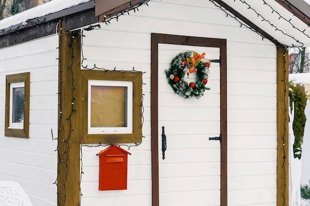 겨울 눈 덮인 도시 공원에 있는 아이들의 편지를 위한 빨간 우편함이 있는 산타클로스 인공 구조물의 흰색 목조 주택. 크리스마스 크리스마스 새 해 휴일 개념입니다.