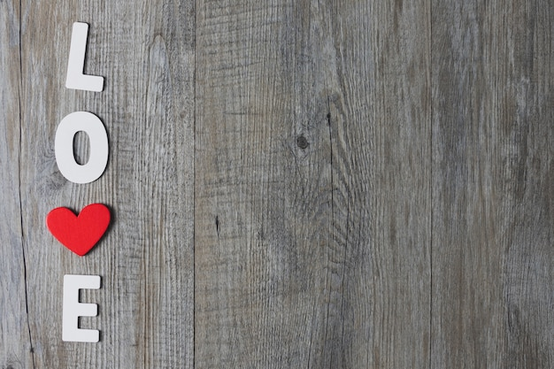 White wooden letters and red wooden hearts on a gray wood background