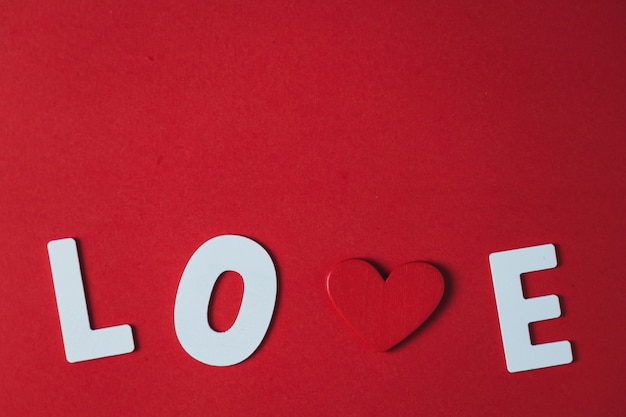 White wooden letters and red wooden hearts on a red background