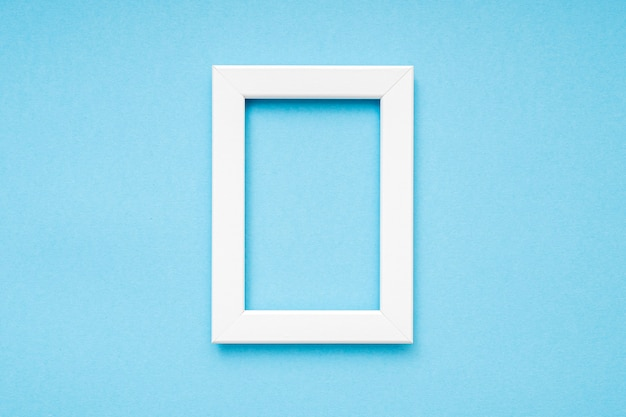 White wooden photo frame on blue surface minimal composition