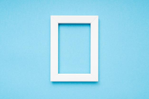 파란색 표면 최소 구성에 흰색 나무 사진 프레임