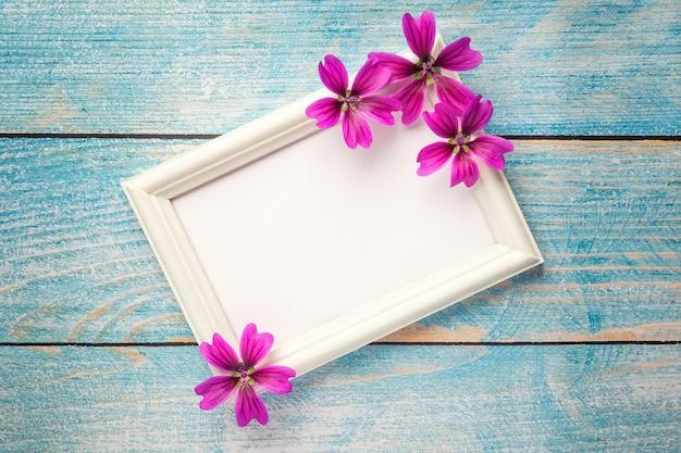 ピンクの紙の背景に紫の花を持つ白い木製フォトフレーム
