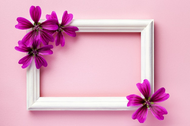 White wooden photo frame with purple flowers on pink paper background,