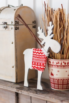 White wooden reindeer with knitted sweater with nordic pattern