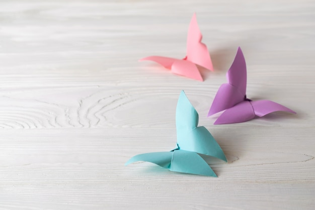 White wooden surface with three colorful origami butterflies with copy space for your text