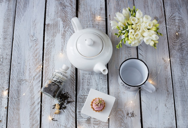 On white wooden table cup, teapot, freesia and cake