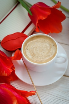 On a white wooden table is a red notebook with tulips, there is a cup of coffee and gingerbread in the form of scarlet lips