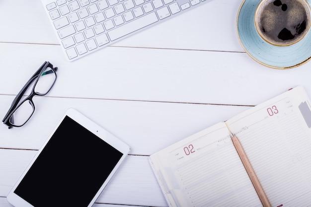 Белый деревянный стол с планшетом, черным кофе, ручкой, блокнотом, клавиатурой и очками. угол обзора сверху с копией пространства