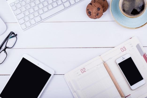 Белый деревянный стол с планшетом, блокнотом, черным кофе, ручкой, телефоном, клавиатурой, печеньем и очками. угол обзора сверху с копией пространства