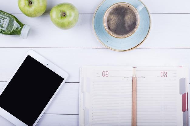 Белый деревянный стол с планшетом, ноутбуком, детоксом и зеленым яблоком. угол обзора сверху с копией пространства