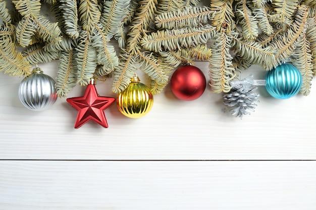 クリスマスツリーの枝やおもちゃと白い木製のテーブル