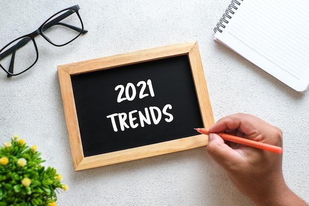 2021년 트렌드에 대해 쓰여진 안경, 펜, 장식용 식물, 칠판이 있는 흰색 나무 테이블. 복사 공간이 있는 평면도, 평평한 위치.