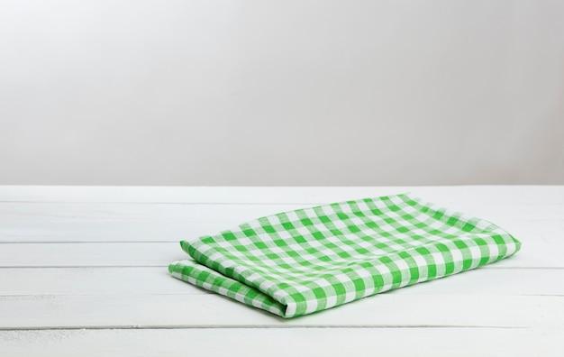 製品のモンタージュのための緑のテーブルクロスと白い木製テーブル