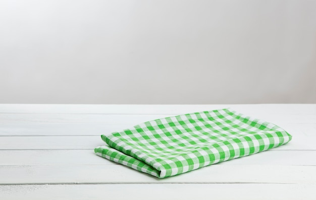 White wooden table with green tablecloth for product montage