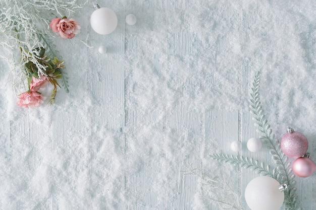 雪とクリスマスの装飾が施された白い木製のテーブル。創造的な冬の上面図。コピースペースのある最小限のフラットレイ。