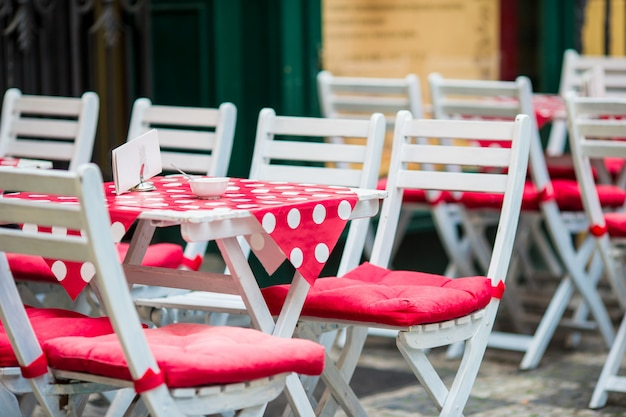 White wooden tables with chairs at summer open air cafe terrace. view of empty outdoor cafe in europe.