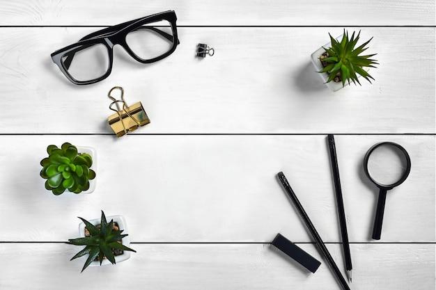 Белая деревянная столешница с черными очками, двумя карандашами, ластиком, лупой и зажимами для папок.