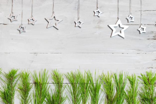 Белый деревянный с еловыми ветками, по контуру звезды.
