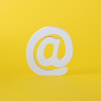 Белое слово at для сообщений электронной почты и интернета. слово для онлайн-общения. желтый летний освещающий фон. виртуальное абстрактное искусство.