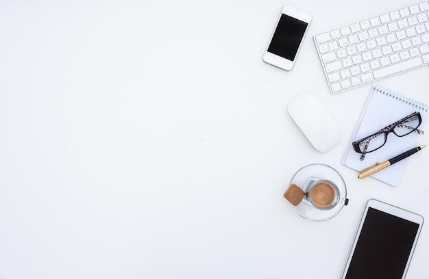 Белое рабочее место. нет людей. чашка кофе, чтобы сделать перерыв. альтернативный открытый офис. устройства и технологии.