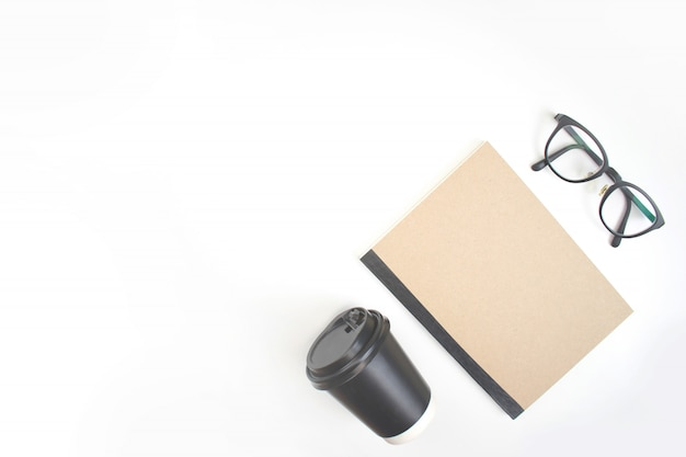 The white workspace of the notebook, coffee and eye glasses