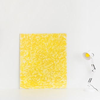 White workspace with yellow picture and reading lamp