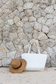 White woven bag and panama hat on a beach with rock wall background, summer vacation concept