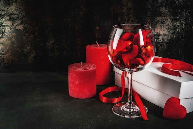White wrapped gift box with red ribbon, rose flower petals in wine glass, with red candle on dark stone background