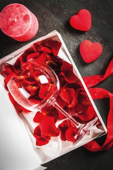White wrapped gift box with red ribbon, with rose flower petals in wine glass