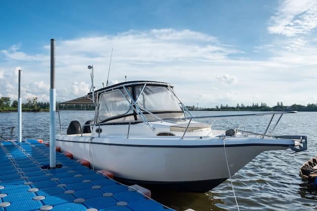 Белая яхта на якоре в реке у пирса