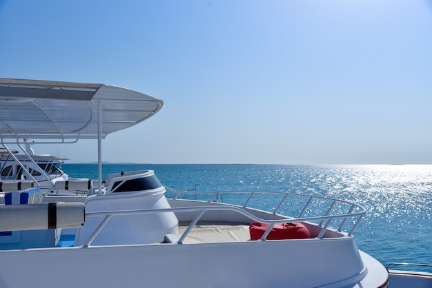 Белая яхта в море против голубого неба.