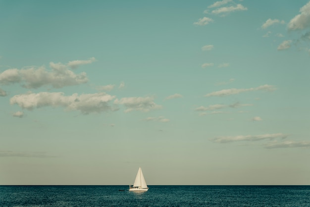 White yacht on the horizon in a quiet sea