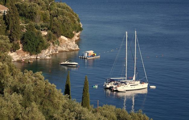 Белая яхта пришвартована в море недалеко от скалистого побережья острова корфу, греция, летние каникулы, отдых