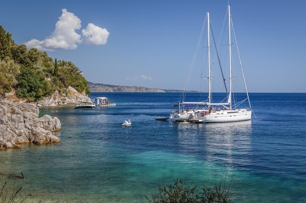 Белая яхта пришвартована в море у скалистого побережья в солнечный летний день летние каникулы в греции