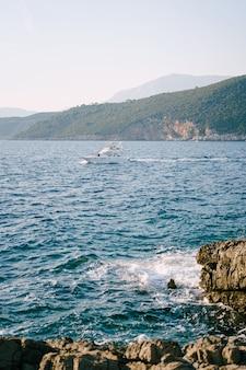 산을 배경으로 그림 같은 해안 근처의 화창한 날에 하얀 요트.