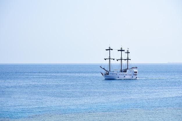海岸に沿って航海する白いヨット